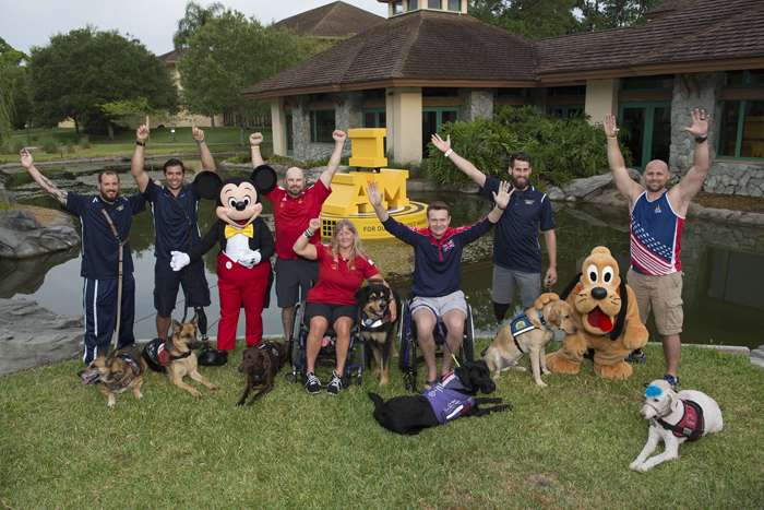 Ahead of the Invictus Games Orlando 2016 closing ceremony, Mickey Mouse and Pluto celebrate service dogs and competitors, (L-R) Leonard Anderson with Azza, August O'Niell with Kai (USA), Luc Martin with Trail, Christine Gauthier with Battak (Canada), Jon Flint with Jester (Great Britain), Stefan LeRoy with Knoxville and Brett Parks with Freedom (USA)