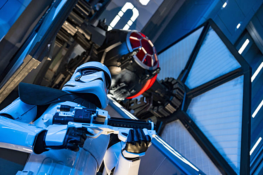 A First Order Stormtrooper stands guard in a Star Destroyer hangar bay beneath a docked TIE fighter in Star Wars: Rise of the Resistance, the groundbreaking new attraction opening Dec. 5, 2019, inside Star Wars: Galaxy's Edge at Disney's Hollywood Studios in Florida and Jan. 17, 2020, at Disneyland Park in California. Guests enter the hangar bay after their ship is caught in the Star Destroyer's tractor beam.