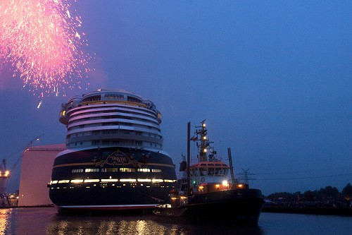 "OCTOBER 30, 2010): As pyrotechnics light the sky, the Disney Dream cruise ship makes its first public appearance Oct. 30, 2010 in Papenburg, Germany as it floats out of an enclosed building dock, pulled by a tugboat, at the Meyer Werft shipyard. Thousands of local residents gathered to see the ""float out"" ceremony. The new ship is scheduled to sail its maiden voyage Jan. 26, 2011 from Port Canaveral, Fla. (Diana Zalucky, photographer)"