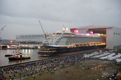 "The Disney Dream cruise ship makes its first public appearance Oct. 30, 2010 in Papenburg, Germany as it begins to exit an enclosed building dock, pulled by a tugboat, at the Meyer Werft shipyard. Thousands of local residents gathered to see the ""float out"" ceremony. The new ship is scheduled to sail its maiden voyage Jan. 26, 2011 from Port Canaveral, Fla."
