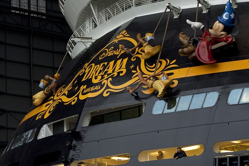"(OCTOBER 30, 2010): A shipyard worker stands under the giant sculpture of Mickey Mouse that hangs from the stern of the Disney Dream cruise ship on Oct. 30, 2010 at the Meyer Werft shipyard in Papenburg, Germany. The new ship made its first public appearance Oct. 30, 2010 as it was pulled by a tugboat out of an enclosed building dock at the Meyer Werft shipyard. Thousands of local residents gathered to see the ""float out"" ceremony. The new ship is scheduled to sail its maiden voyage Jan. 26, 2011 from Port Canaveral, Fla. (Diana Zalucky, photographer)"