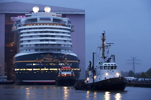 "(OCTOBER 30, 2010): The Disney Dream cruise ship makes its first public appearance Oct. 30, 2010 in Papenburg, Germany as it begins to exit an enclosed building dock, pulled by a tugboat, at the Meyer Werft shipyard. Thousands of local residents gathered to see the ""float out"" ceremony. The new ship is scheduled to sail its maiden voyage Jan. 26, 2011 from Port Canaveral, Fla. (Diana Zalucky, photographer)"